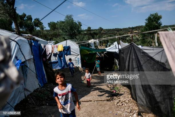 Children stand outside tents at a camp next to the Moria refugee camp in the island of Lesbos on August 5 2018