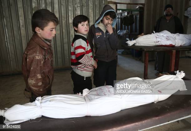 Children stand over the body of a child at a makeshift hospital, following an airstrike in the rebel-held besieged town of Arbin, in the eastern...