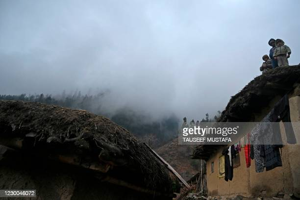 Children stand over their mud house built on top of a mountain amid heavy fog on the outskirts of Srinagar on December 10, 2020.