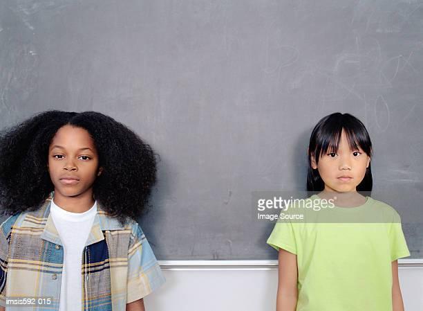 Kinder stehen gegen Tafel