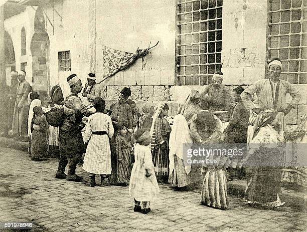 Children standing around sweet sellers in Damascus Syria in 1894