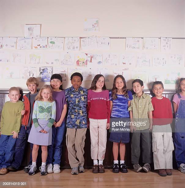Children (8-9), standing beside classroom wall display, portrait