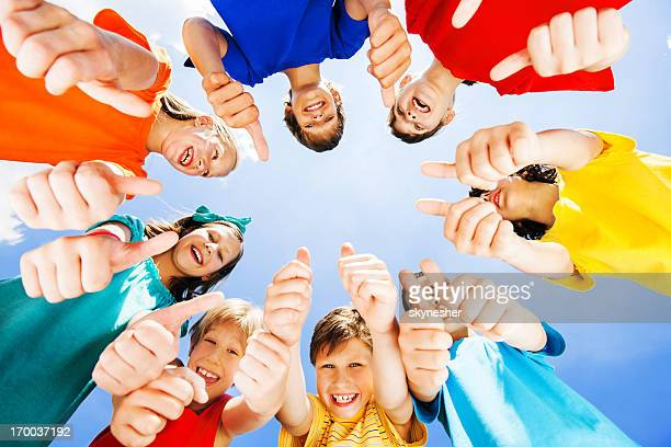 children standing in circle and showing thumbs up - human body part stock pictures, royalty-free photos & images