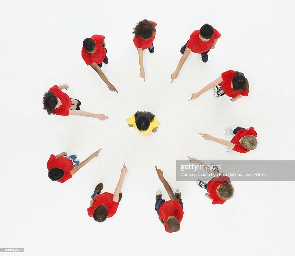 Children standing in circle pointing to centre : Stock Photo