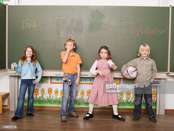children (4-7) standing in front of blackboard, portrait - 鼻をつまむ ストックフォトと画像