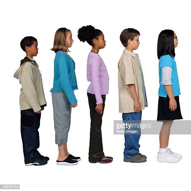 children (11-13) standing in line, side view - somente crianças imagens e fotografias de stock