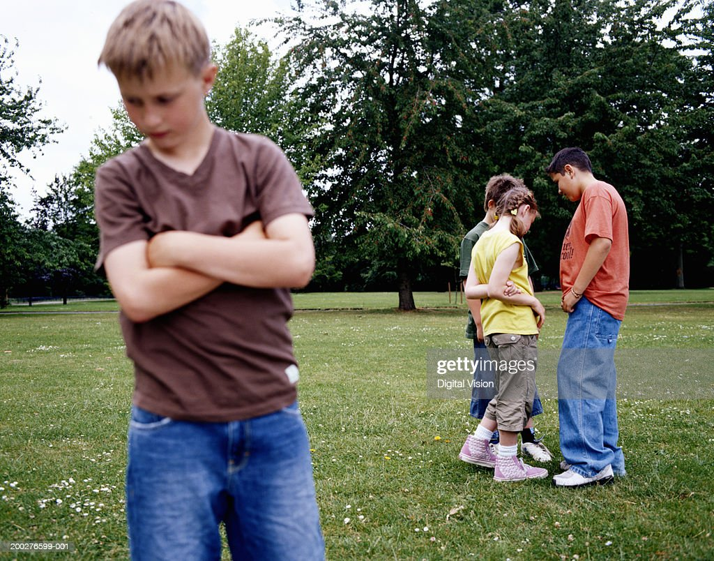 Children (9-12) standing in park, boy with arms crossed in foreground : Stock Photo