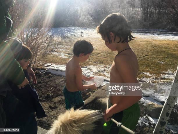 Kinder stehen in der Sonne im Winter nach dem Schwimmen