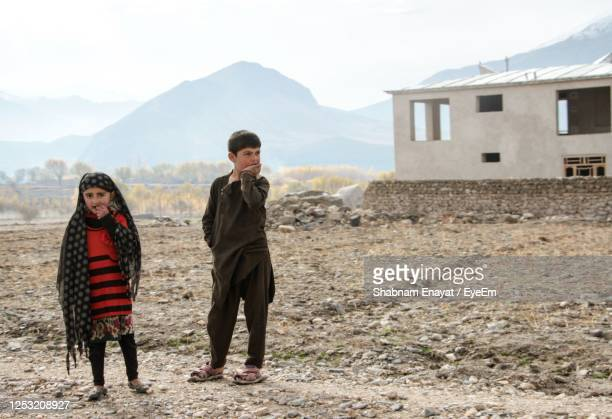 children standing on field against sky - afghanistan stock pictures, royalty-free photos & images