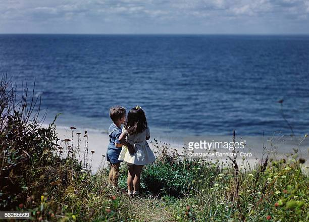 Children standing on shoreline looking out to ocean