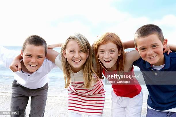 Niños de pie junto a la playa