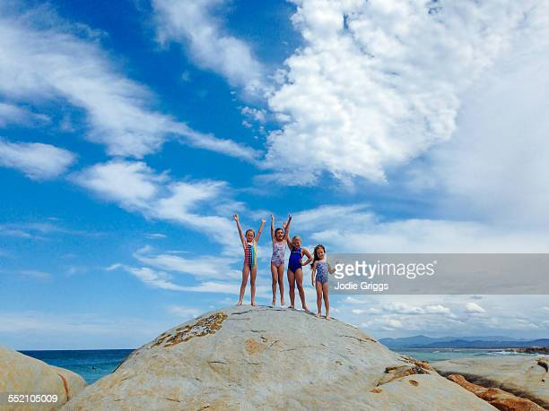Children standing together on large rock at beach