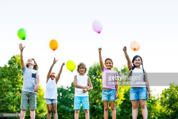 children standing with balloons - releasing stock pictures, royalty-free photos & images