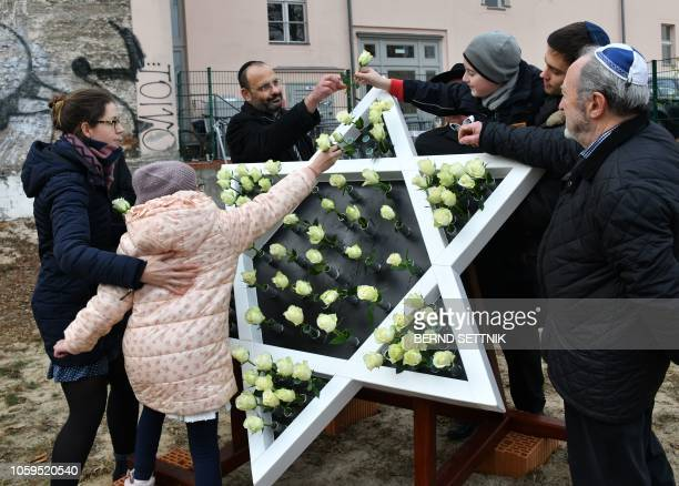 Children stick white roses into a Star of David sculpture at the construction site of a new synagogue in Potsdam eastern Germany on November 9 the...