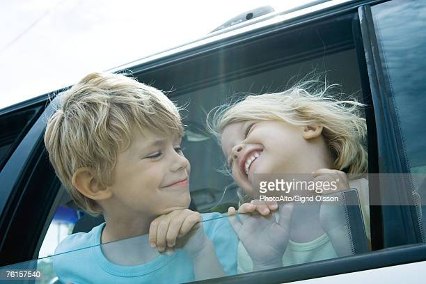 Children sticking heads out of car window