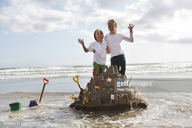 children stood on sandcastle surrounded by water - cornish flag stock pictures, royalty-free photos & images