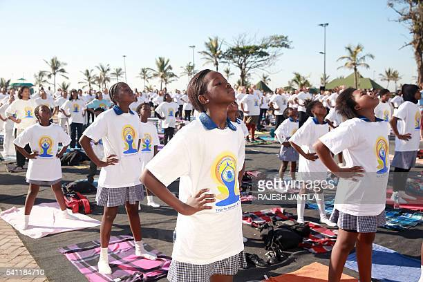 Children stretch as hundreds of people take part in a yoga session as part of the International Day of Yoga at the amphitheatre lawns at North Beach...