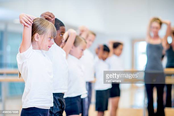 children stretching in gym class - educational subject stock photos and pictures