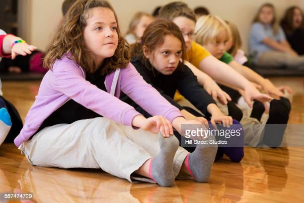 Children stretching legs in gym class