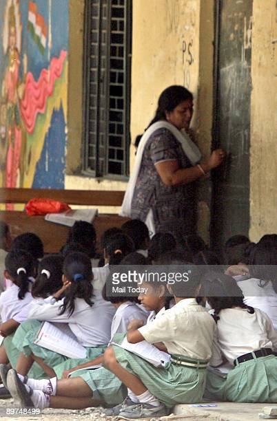 Children study outside their classrooms at an MCD school in New Delhi on Friday August 7 2009