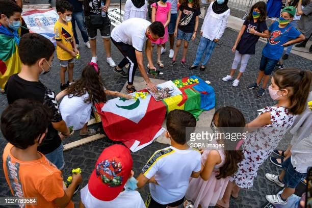 Children supporters of the popular Rif Movement wearing masks are seen placing flowers on the simulated coffin covered with the flags of the Amazigh...