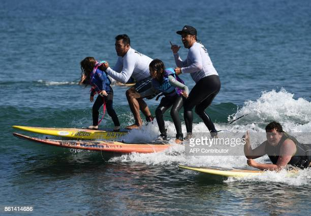Children surf with members of the 'Mighty Under Dogs' organization during a day of 'Surf Therapy' to help about 40 local children living with social...