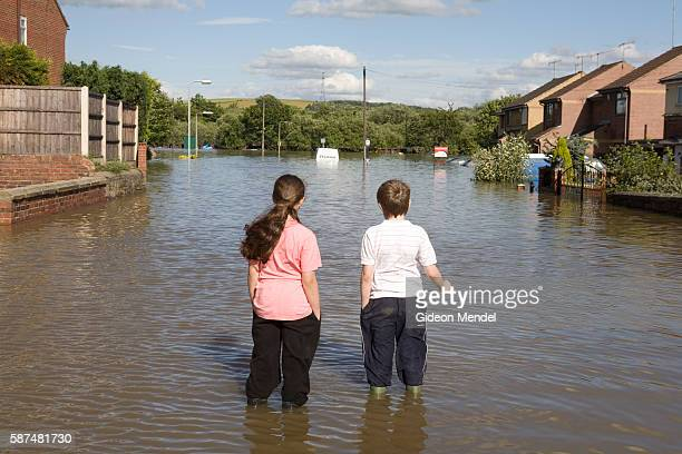 Children survey one of the flooded streets of Catcliffe village This was one of the communities flooded when a freak tropical storm unleashed a...