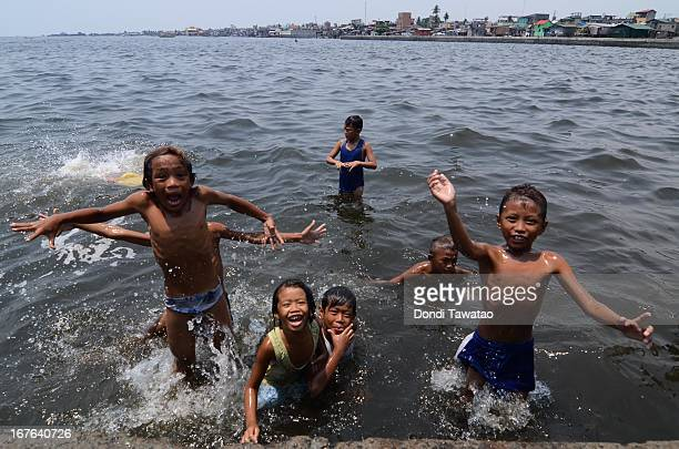 Children swim in the murky waters of Navotas de Bay on April 27, 2013 in Manila, Philippines. Despite small rainshowers, temperatures soared from 35...