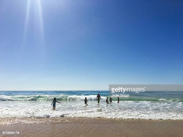 Children swimming at beach with adult on hot day