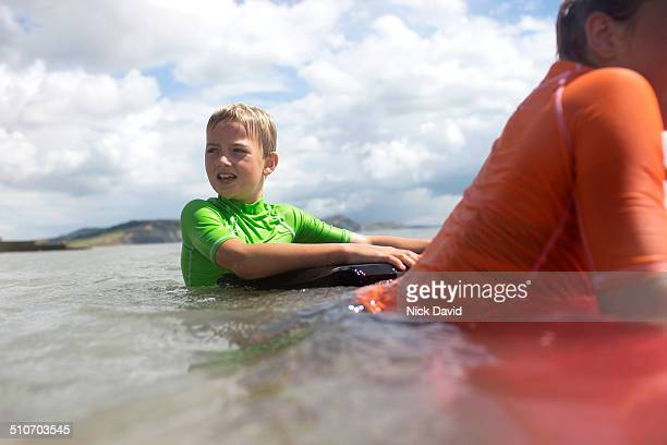 Children swimming in the sea with bodyboards