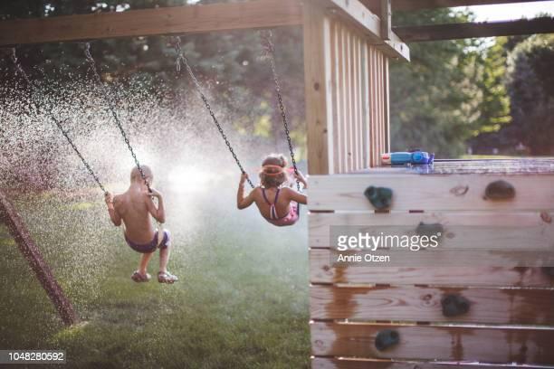 Children Swinging Into a Sprinkler