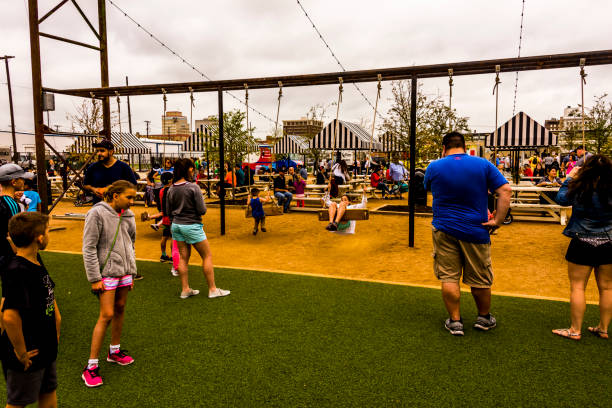 WACO, TX, USA  MARCH 18, 2017: Children swinging on swings in the waiting area of Magnolia Market.