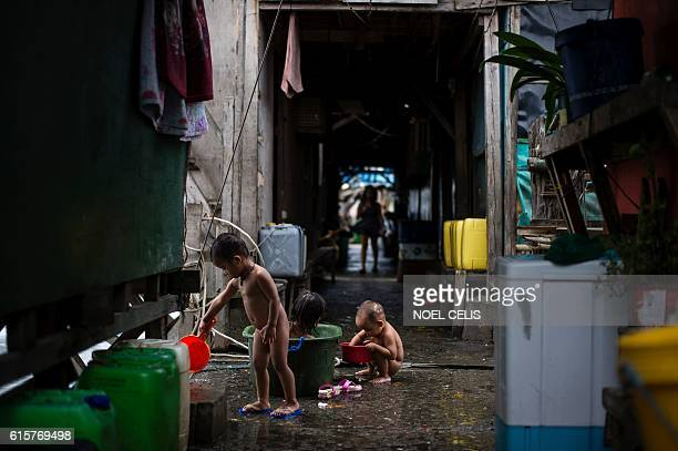 Children take a bath at shanties at the breakwater at Baseco Tondo in Manila on October 20 2016 One of the most powerful typhoons to ever hit the...