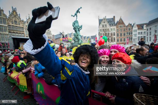 Children take a selfie with a man dressedas Zwarte Piet during the traditionnal arrival of Sinterklaas on November 12 2016 in Antwerp Black Pete is...