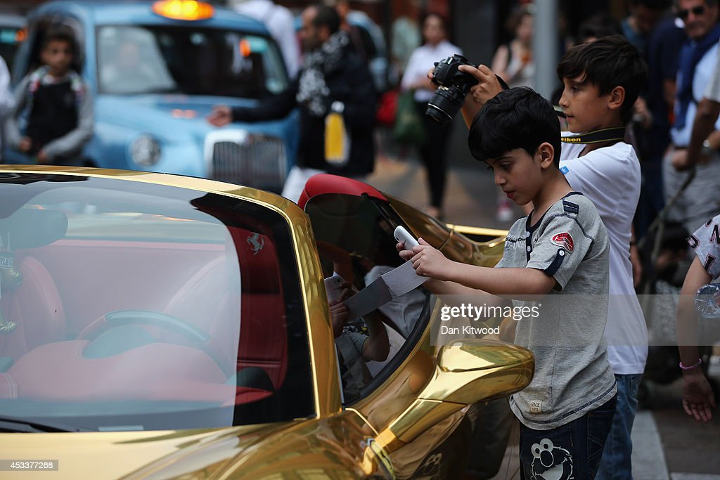 Children take photographs of a Gold Ferrari in Knightsbridge on August 8, 2014 in London, England. Tourists and car enthusiasts have been flocking to the wealthy London district to see some of the world's most expensive and extravagant super cars. Many of the rich owners from Saudi Arabia and Kuwait come to London to escape the summer heat at home and to show off their cars before moving on to other European cities such as Paris and Cannes.