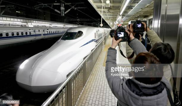 Children take photos of the new N700S bullet train arriving at Shizuoka Station during a test run in Shizuoka prefecture Japan on March 23 2018 The...