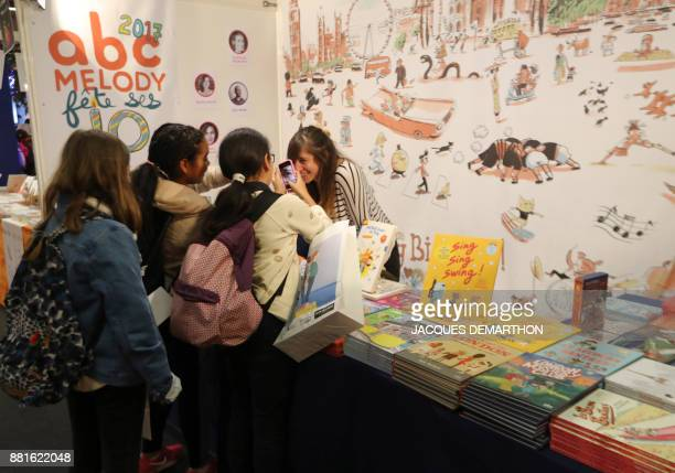 Children take pictures at the Salon du livre et de la presse jeunesse in Montreuil eastern Paris on November 29 2017 DEMARTHON