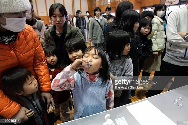 Children take potassium iodide to avoid thyroid cancer after evacuated from the 10km radius from the Fukushima Daiichi Nuclear Power Plant after an...