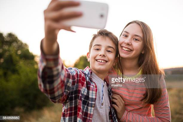 Children take selfie with a smart phone in nature