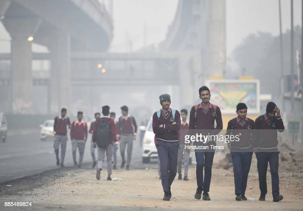 Children taking precautions against cold weather and smog at Green Park on December 4 2017 in New Delhi India Air quality remained very poor with air...