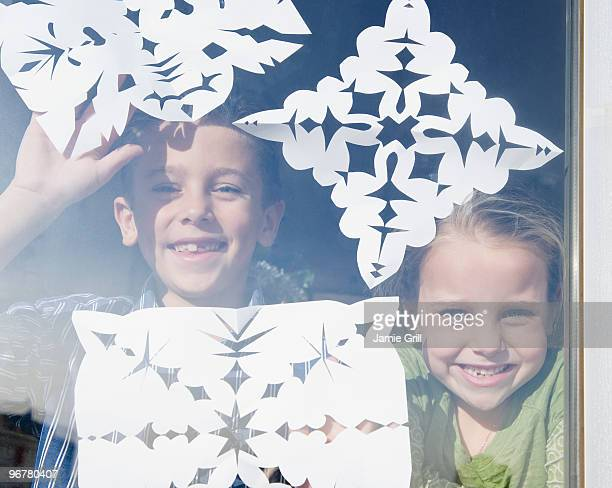 children taping paper snowflakes to window  - art and craft stock pictures, royalty-free photos & images