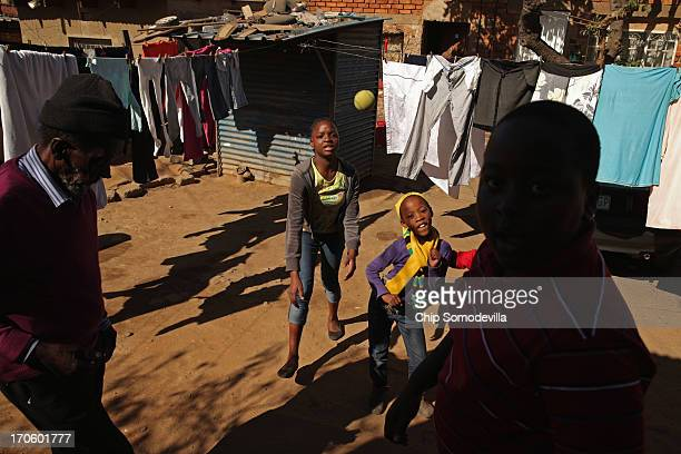 Children throw as they play ball in an alley behind shacks in the Alexandra Township June 15 2013 in Johannesburg South Africa former South African...