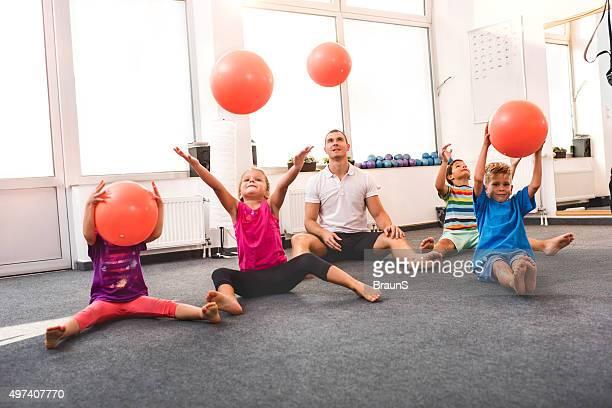 Enfants balancer de balles sur un cours d'entraînement avec un entraîneur.