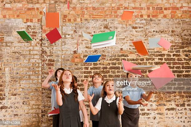 Children throwing books in the air