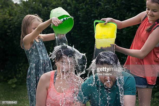 Children throwing buckets of water over adults