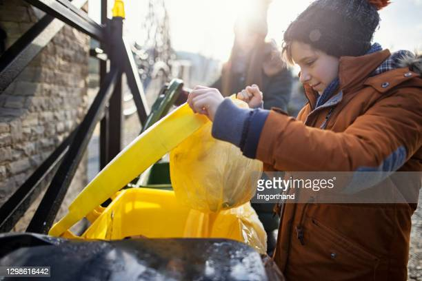 children throwing out segregated garbage to separate bins - absence stock pictures, royalty-free photos & images