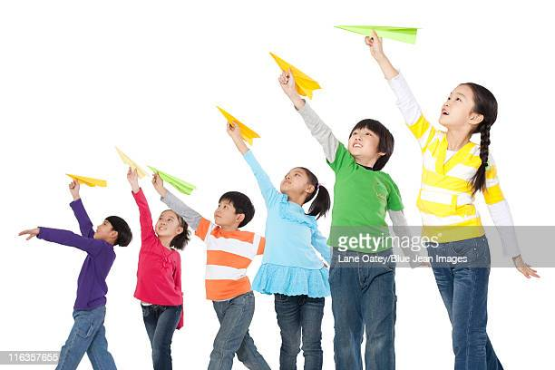 Children throwing paper airplanes