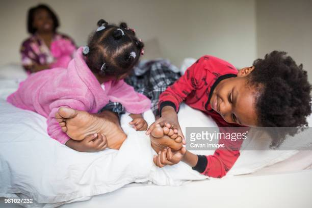 children tickling fathers feet on bed - tickling feet stock photos and pictures