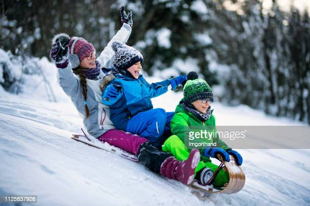 children tobogganing in winter forest. - tobogganing stock pictures, royalty-free photos & images