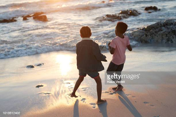 Children together playing on beach by the edge of the sea